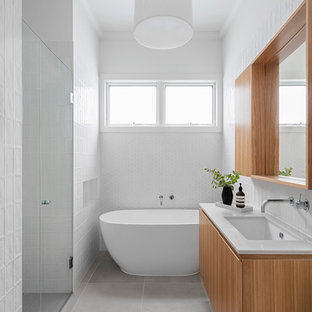 Mid-sized contemporary bathroom in Melbourne with medium wood cabinets, a freestanding tub, white tile, porcelain floors, an undermount sink, engineered quartz benchtops, grey floor and white walls.