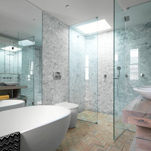 This is an example of a mid-sized contemporary bathroom in Sydney with medium wood cabinets, a double shower, grey walls, brick floors, a vessel sink, wood benchtops, gray tile and brown benchtops.