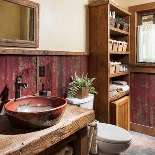 Ejemplo de cuarto de baño rústico, pequeño, con armarios abiertos, puertas de armario marrones, sanitario de dos piezas, paredes beige, suelo de cemento, lavabo sobreencimera, encimera de madera y suelo rojo