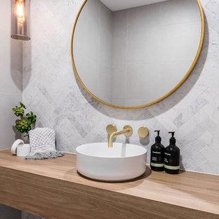 Foto de cuarto de baño con ducha, moderno, de tamaño medio, con armarios abiertos, puertas de armario de madera oscura, sanitario de dos piezas, baldosas y/o azulejos blancos, paredes grises, lavabo encastrado, encimera de madera, suelo gris y encimeras azules