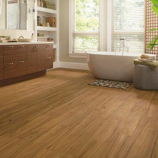Bathroom - large transitional master medium tone wood floor and beige floor bathroom idea in Other with flat-panel cabinets, medium tone wood cabinets, a one-piece toilet, beige walls, a vessel sink and limestone countertops