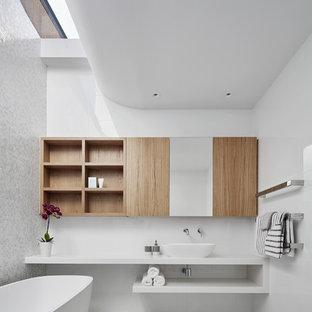 Idee per una stanza da bagno minimal di medie dimensioni con nessun'anta, vasca freestanding, piastrelle bianche, piastrelle di vetro, pavimento con piastrelle a mosaico, lavabo a bacinella, top in superficie solida, top bianco, ante in legno chiaro, pareti bianche e pavimento bianco