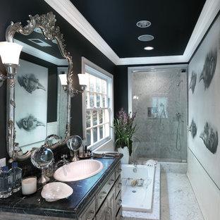 ロサンゼルスのトラディショナルスタイルのおしゃれな浴室 (オーバーカウンターシンク、レイズドパネル扉のキャビネット、ヴィンテージ仕上げキャビネット、ドロップイン型浴槽、アルコーブ型シャワー、白いタイル、黒い壁) の写真