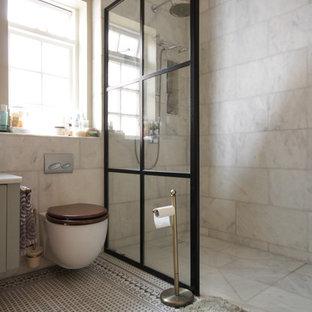 Ejemplo de cuarto de baño infantil, bohemio, de tamaño medio, con ducha abierta, sanitario de pared, baldosas y/o azulejos de mármol, paredes verdes, suelo de baldosas de cerámica, lavabo tipo consola, encimera de mármol, suelo negro y ducha abierta