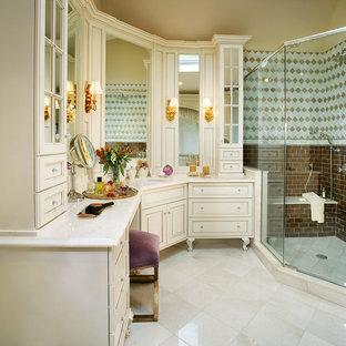 Modelo de cuarto de baño tradicional, de tamaño medio, con lavabo bajoencimera, armarios tipo mueble, puertas de armario blancas, encimera de mármol, ducha esquinera, sanitario de una pieza y suelo de mármol