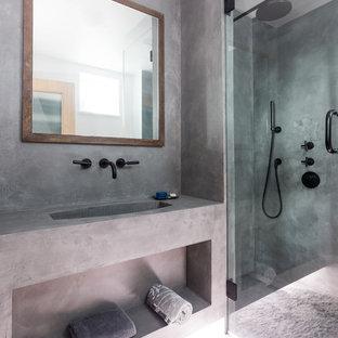 Industriell inredning av ett litet grå grått badrum med dusch, med öppna hyllor, grå skåp, en hörndusch, grå väggar, ett integrerad handfat, bänkskiva i betong, betonggolv och grått golv