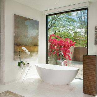 Foto på ett stort funkis en-suite badrum, med ett fristående badkar, en kantlös dusch, vita väggar, ett fristående handfat, släta luckor, skåp i mellenmörkt trä, en toalettstol med hel cisternkåpa, vit kakel, marmorkakel, marmorgolv, bänkskiva i kvarts, vitt golv och med dusch som är öppen