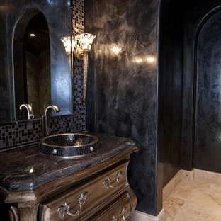 Design ideas for an expansive mediterranean shower room in Houston with a vessel sink, freestanding cabinets, dark wood cabinets, marble worktops, a two-piece toilet, black tiles, stone tiles, black walls and travertine flooring.