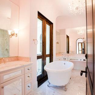 На фото: класса люкс огромные детские ванные комнаты в средиземноморском стиле с настольной раковиной, стеклянными фасадами, белыми фасадами, мраморной столешницей, ванной на ножках, душем в нише, раздельным унитазом, белой плиткой, каменной плиткой, розовыми стенами и мраморным полом