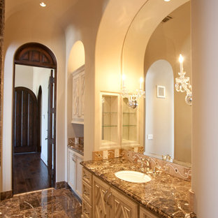 Inspiration for an expansive mediterranean ensuite bathroom in Houston with a built-in sink, freestanding cabinets, beige cabinets, marble worktops, a freestanding bath, an alcove shower, a two-piece toilet, brown tiles, stone tiles, beige walls and marble flooring.