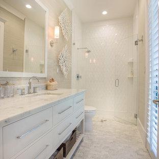 Ispirazione per una stanza da bagno chic di medie dimensioni con lavabo sottopiano, ante lisce, ante bianche, top in marmo, doccia a filo pavimento e piastrelle bianche