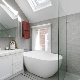 This is an example of a scandinavian master bathroom in Sydney with shaker cabinets, white cabinets, a freestanding tub, gray tile, granite benchtops, a hinged shower door, white benchtops, a curbless shower, grey walls, a vessel sink and grey floor.