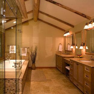 Exemple d'une grande salle de bain principale montagne avec un placard à porte shaker, des portes de placard en bois clair, une baignoire en alcôve, une douche d'angle, un mur beige, un sol en travertin et un lavabo encastré.
