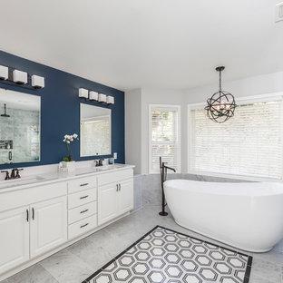 シアトルの巨大なおしゃれなマスターバスルーム (シェーカースタイル扉のキャビネット、白いキャビネット、置き型浴槽、洗い場付きシャワー、一体型トイレ、白いタイル、大理石タイル、青い壁、大理石の床、アンダーカウンター洗面器、珪岩の洗面台、白い床、シャワーカーテン、白い洗面カウンター) の写真