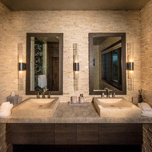 Foto de cuarto de baño principal, rural, de tamaño medio, con lavabo sobreencimera, armarios con paneles lisos, puertas de armario de madera en tonos medios, baldosas y/o azulejos de piedra, paredes beige y encimera de granito