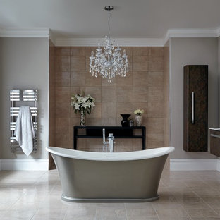 Expansive classic ensuite bathroom in Hertfordshire with a wall-mounted sink, flat-panel cabinets, dark wood cabinets, a freestanding bath, a one-piece toilet, brown tiles and grey walls.