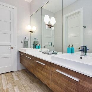 Ejemplo de cuarto de baño con ducha, actual, con armarios con paneles lisos, puertas de armario de madera oscura, baldosas y/o azulejos blancos, paredes blancas, suelo de madera en tonos medios, lavabo sobreencimera y suelo marrón