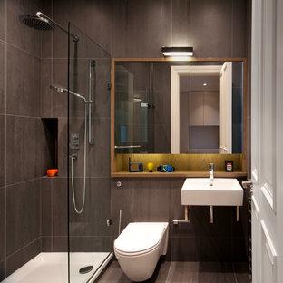 Foto de cuarto de baño con ducha, contemporáneo, pequeño, con lavabo suspendido, ducha esquinera, sanitario de pared, baldosas y/o azulejos marrones, baldosas y/o azulejos de piedra y paredes grises