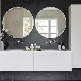 Großes Modernes Badezimmer mit flächenbündigen Schrankfronten, weißen Schränken, freistehender Badewanne, offener Dusche, Toilette mit Aufsatzspülkasten, schwarz-weißen Fliesen, schwarzer Wandfarbe, Unterbauwaschbecken, Mineralwerkstoff-Waschtisch, schwarzem Boden und Zementfliesen in London