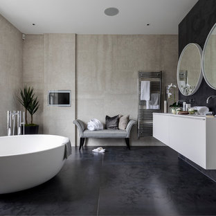 Photo of a large contemporary family bathroom in London with flat-panel cabinets, white cabinets, a freestanding bath, a walk-in shower, a one-piece toilet, black and white tiles, black walls, cement flooring, a submerged sink, solid surface worktops and black floors.