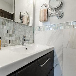 Diseño de cuarto de baño principal, clásico renovado, de tamaño medio, con armarios con paneles lisos, puertas de armario negras, bañera empotrada, combinación de ducha y bañera, sanitario de una pieza, baldosas y/o azulejos azules, baldosas y/o azulejos grises, baldosas y/o azulejos blancos, baldosas y/o azulejos en mosaico, paredes azules, suelo laminado, lavabo integrado, suelo gris y ducha con cortina