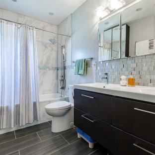 Esempio di una stanza da bagno padronale classica di medie dimensioni con ante lisce, ante nere, vasca ad alcova, vasca/doccia, WC monopezzo, piastrelle blu, piastrelle grigie, piastrelle bianche, piastrelle a mosaico, pareti blu, pavimento in laminato, lavabo integrato, pavimento grigio e doccia con tenda