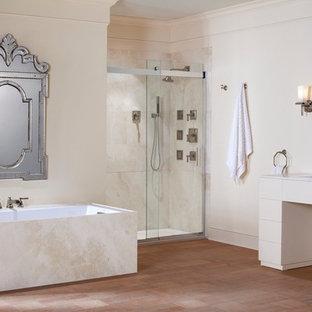Diseño de cuarto de baño principal, tradicional, grande, con lavabo bajoencimera, encimera de mármol, bañera encastrada sin remate, ducha a ras de suelo, baldosas y/o azulejos beige, baldosas y/o azulejos de piedra, armarios abiertos, puertas de armario beige, sanitario de una pieza, paredes beige y suelo de corcho