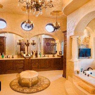 Ispirazione per un'ampia stanza da bagno padronale mediterranea con ante in legno bruno, vasca da incasso, piastrelle beige, piastrelle in pietra, pareti beige, pavimento in travertino, lavabo sottopiano, top in granito e ante con bugna sagomata