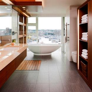 Modernes Badezimmer mit freistehender Badewanne, Unterbauwaschbecken, flächenbündigen Schrankfronten, hellbraunen Holzschränken, Granit-Waschbecken/Waschtisch, offener Dusche, Wandtoilette, offener Dusche und oranger Waschtischplatte in Vancouver
