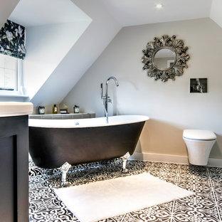 Foto de cuarto de baño principal con armarios estilo shaker, puertas de armario negras, bañera con patas, sanitario de pared, paredes grises, suelo con mosaicos de baldosas y suelo negro