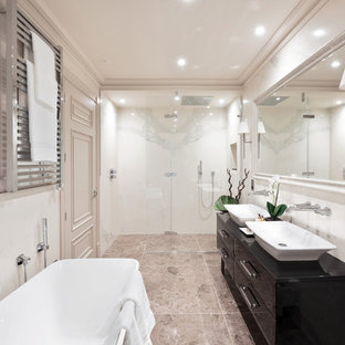 Traditional ensuite bathroom in London with flat-panel cabinets, black cabinets, a freestanding bath, a built-in shower, white tiles, white walls, a vessel sink, brown floors, a hinged door and black worktops.