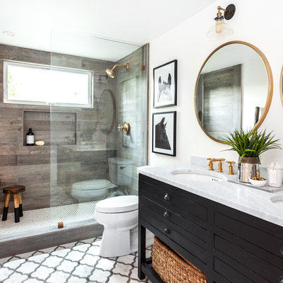 Small cottage 3/4 multicolored tile and stone tile marble floor doorless shower photo in Sacramento with furniture-like cabinets, black cabinets, a one-piece toilet, white walls, an undermount sink and marble countertops