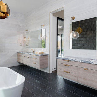 Inspiration for a contemporary master bathroom in Las Vegas with flat-panel cabinets, an undermount sink, marble benchtops, multi-coloured benchtops, light wood cabinets, a freestanding tub, white tile and black floor.