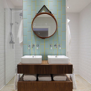 Corner shower - mid-sized industrial blue tile and subway tile corner shower idea in London with a vessel sink, wood countertops, white walls and brown countertops