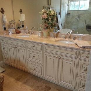 Inspiration för ett mellanstort shabby chic-inspirerat en-suite badrum, med luckor med upphöjd panel, beige skåp, ett badkar med tassar, en dusch i en alkov, en toalettstol med hel cisternkåpa, beige kakel, keramikplattor, beige väggar, travertin golv, ett undermonterad handfat och granitbänkskiva