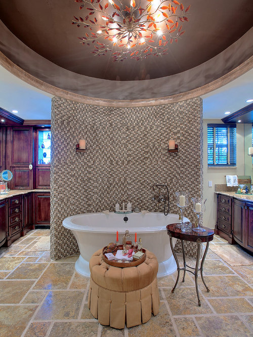 elegant beige tile freestanding bathtub photo in new york with raised panel cabinets and dark