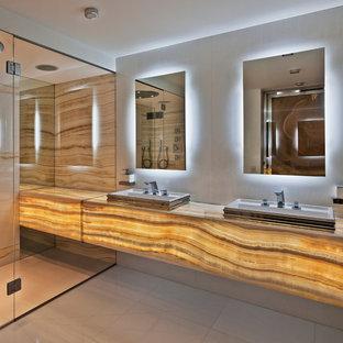Modelo de cuarto de baño principal, contemporáneo, grande, con armarios abiertos, puertas de armario amarillas, ducha abierta, baldosas y/o azulejos blancos, losas de piedra, paredes blancas, suelo de mármol, encimera de ónix y lavabo encastrado
