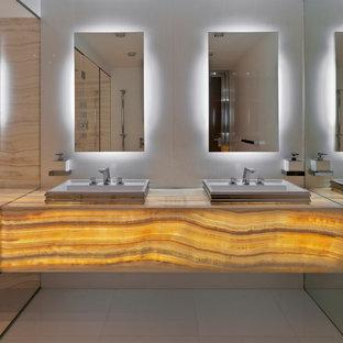 ニューヨークの広いコンテンポラリースタイルのおしゃれなマスターバスルーム (オープン型シャワー、白いタイル、石スラブタイル、白い壁、大理石の床、オニキスの洗面台、オーバーカウンターシンク、フラットパネル扉のキャビネット、オレンジのキャビネット) の写真