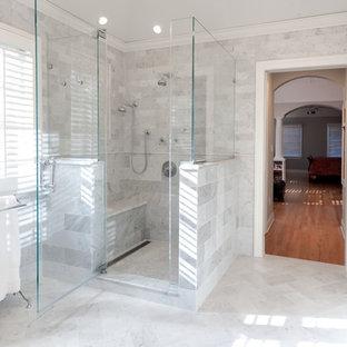 Modelo de cuarto de baño principal, clásico, grande, con lavabo bajoencimera, puertas de armario blancas, encimera de mármol, bañera exenta, ducha esquinera, baldosas y/o azulejos blancos, baldosas y/o azulejos de piedra, paredes grises, suelo de mármol, armarios con rebordes decorativos y sanitario de una pieza