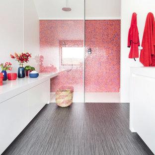 Modelo de cuarto de baño contemporáneo con armarios con paneles lisos, puertas de armario blancas, ducha empotrada, baldosas y/o azulejos multicolor, baldosas y/o azulejos naranja, baldosas y/o azulejos rosa, baldosas y/o azulejos rojos, baldosas y/o azulejos en mosaico, paredes blancas, suelo vinílico, suelo gris, ducha abierta y encimeras blancas