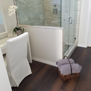 Foto di una stanza da bagno padronale minimalista di medie dimensioni con doccia alcova, piastrelle grigie, piastrelle in gres porcellanato, pareti beige, pavimento in vinile, pavimento marrone e porta doccia a battente