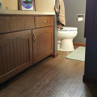 Imagen de cuarto de baño con ducha, de estilo de casa de campo, pequeño, con armarios con paneles empotrados, puertas de armario marrones, bañera encastrada, sanitario de dos piezas, baldosas y/o azulejos amarillos, baldosas y/o azulejos de cerámica, paredes grises, suelo vinílico, lavabo encastrado y encimera de laminado