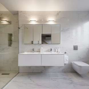 Inspiration for a modern ensuite bathroom in London with flat-panel cabinets, white cabinets, a walk-in shower, a wall mounted toilet, grey tiles, white tiles, multi-coloured walls, an integrated sink and an open shower.