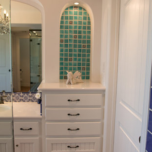 This is an example of a medium sized mediterranean ensuite bathroom in Austin with recessed-panel cabinets, white cabinets, a corner shower, blue tiles, multi-coloured tiles, ceramic tiles, white walls, terracotta flooring, a submerged sink, brown floors, a shower curtain and white worktops.