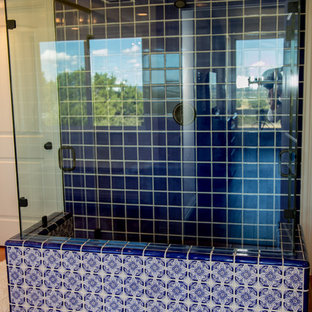 Photo of a large mediterranean ensuite bathroom in Austin with recessed-panel cabinets, white cabinets, an alcove shower, blue tiles, ceramic tiles, white walls, terracotta flooring, a submerged sink, marble worktops, brown floors, a hinged door and white worktops.