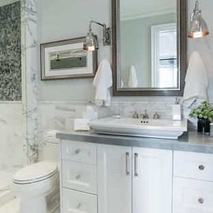 Diseño de cuarto de baño con ducha, tradicional, de tamaño medio, con puertas de armario blancas, baldosas y/o azulejos blancos, lavabo sobreencimera, armarios con paneles empotrados, baldosas y/o azulejos de piedra, suelo con mosaicos de baldosas, ducha empotrada, sanitario de dos piezas, paredes grises, encimera de vidrio, suelo blanco y encimeras grises