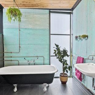 Diseño de cuarto de baño principal, industrial, de tamaño medio, con bañera con patas, baldosas y/o azulejos de metal, paredes verdes, suelo de baldosas de cerámica, lavabo encastrado y suelo negro