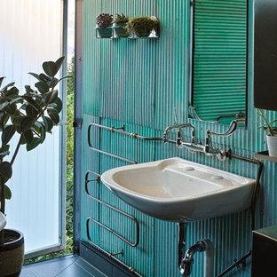 Modelo de cuarto de baño principal, bohemio, de tamaño medio, con bañera con patas, baldosas y/o azulejos de metal, paredes verdes, suelo de baldosas de cerámica, lavabo encastrado y suelo negro