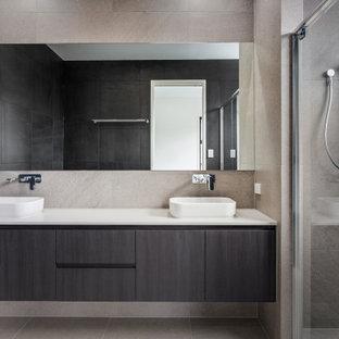 Inspiration för ett mellanstort gul gult en-suite badrum, med möbel-liknande, svarta skåp, ett fristående badkar, en dusch i en alkov, svart kakel, porslinskakel, klinkergolv i porslin, ett fristående handfat, bänkskiva i kvarts, grått golv och dusch med gångjärnsdörr