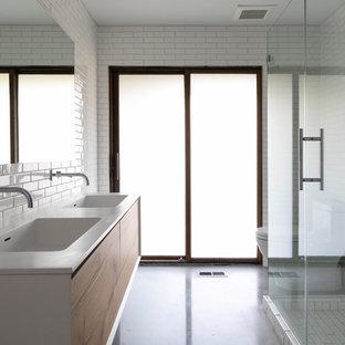 Imagen de cuarto de baño moderno con armarios con paneles lisos, puertas de armario de madera oscura, ducha esquinera, baldosas y/o azulejos blancos, paredes amarillas, suelo de cemento, lavabo integrado, suelo gris, ducha con puerta con bisagras y encimeras blancas